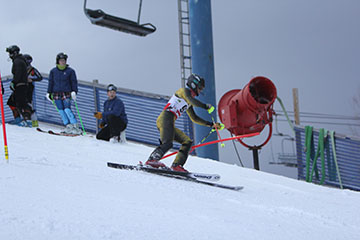 Senior Tommy Kemp races down Mt. Holly in a slalom race against holly oxford.  Tommy races through the gates to victory.