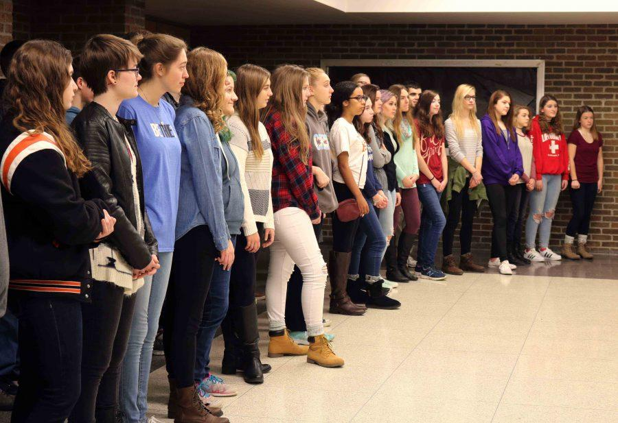 Brad Wright's Varsity Vocal students wait to welcome the school board as they enter the lobby of the high school.