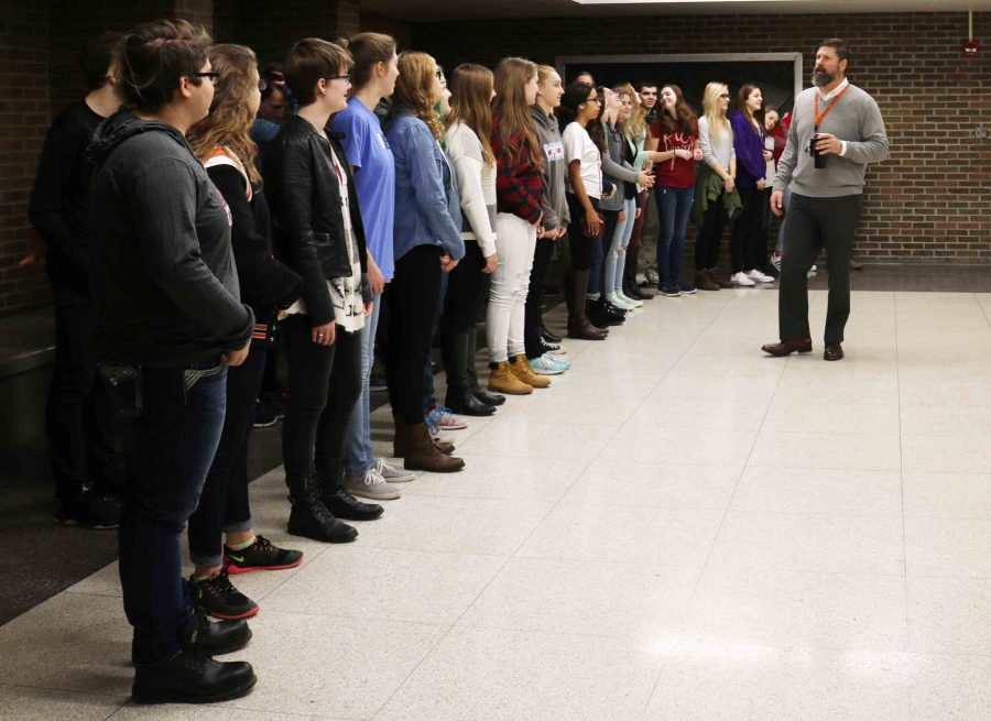 Brad Wright discusses pitch and attitude with his Varsity Vocals students to prep them before singing to the school board.