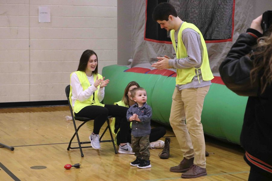 Volunteering at the expo, seniors Kelly Farren and Patrick Conroy entertain a little boy. NHS members volunteering during the spring expo at the kid center.