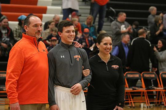 Junior Aj Lepage poses with his parents at parent night. The varsity boys basketball players  celebrated their last home game.