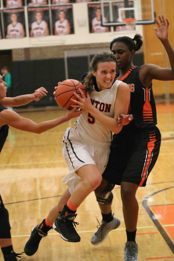 Determained to make a basket, senior Emma Evo pushes her way through the Flushing Raiders defense. The girls played a very close game against the Raiders.
