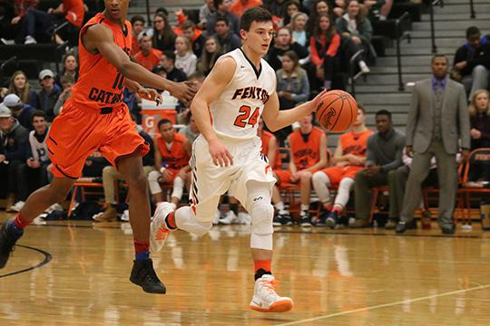 Dribbling the ball down the court, junior Aj Lepage by passes a defender. The boys played a great game against Powers eventually pulling out another win.