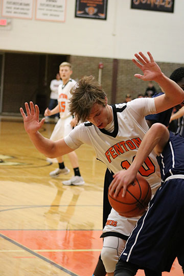 In attempt to block Powers player from shooting Sophomore Logan Welch stays determined to get the ball for Fenton.