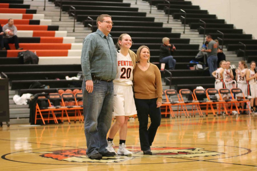 Smiling with her parents, sophomore Erin Carter awaits the flash of the photographer. The girls basketball had a team night and they all got pictures taken with their parents and had smiles on their faces throughout the night.