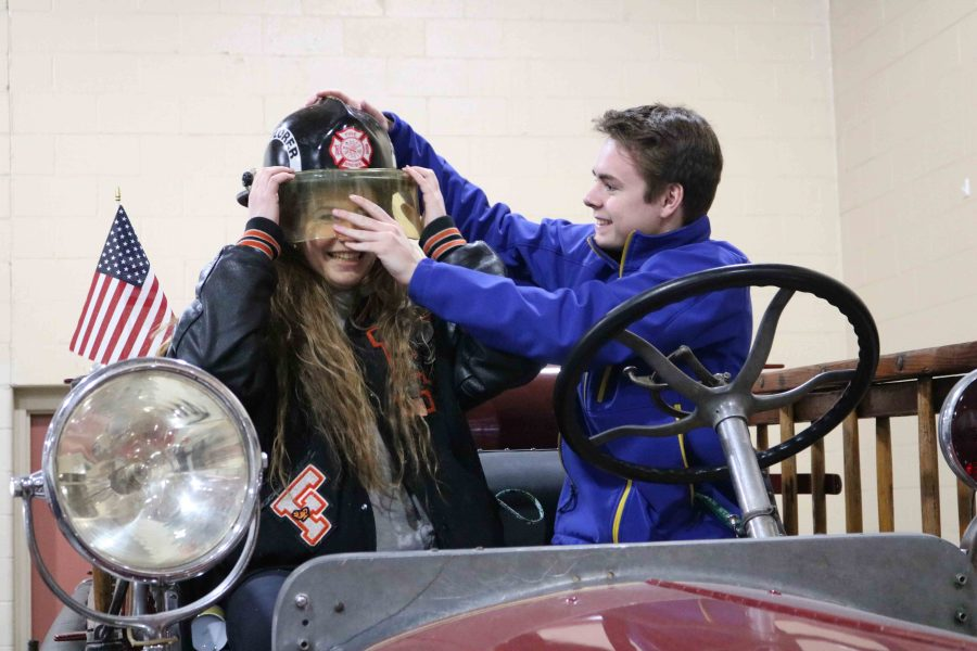 Sitting atop an old fire truck, senior Colin O'Connor helps senior Abby Quesnelle try on a fireman's helmet. The students went on a field trip to the fire station to help them learn more about their arson unit in forensics science.