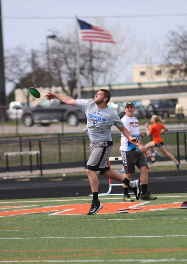 Putting all of his effort into practicing his discus throw,  junior Austin Waligora prepares for the upcoming track meet against Brandon.