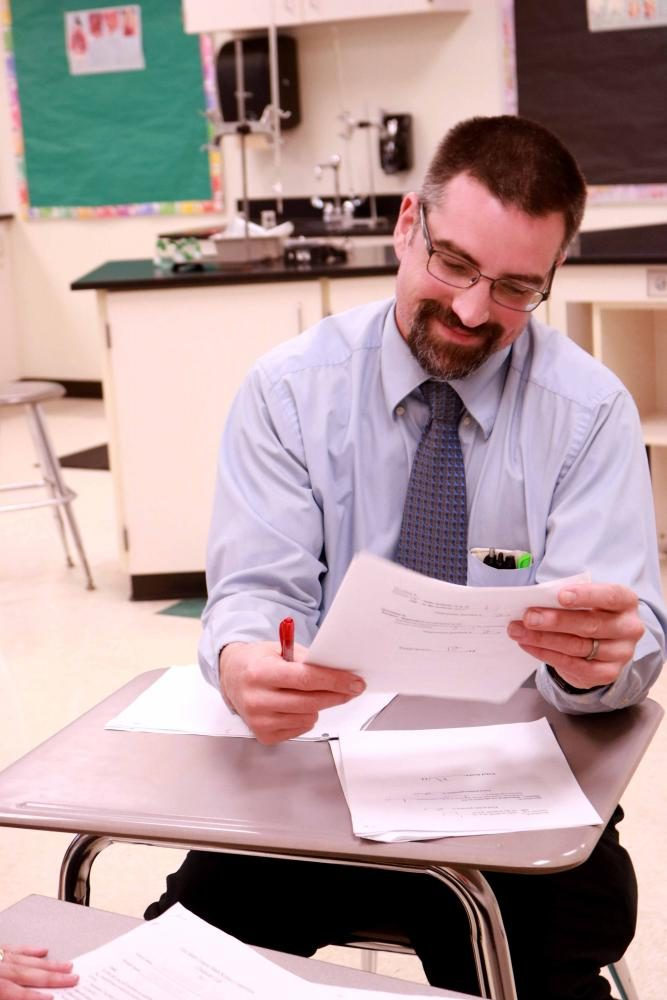At the annual Math and Science competition, science teacher Mr. Kasak smiles while grading student's papers.