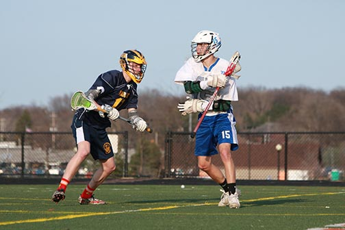 Senior Dylan Miesch dodges a defending opponent player in his varsity lacrosse game. Miesch has been on Fenton Linden wolves lacrosse team for the past three years.
