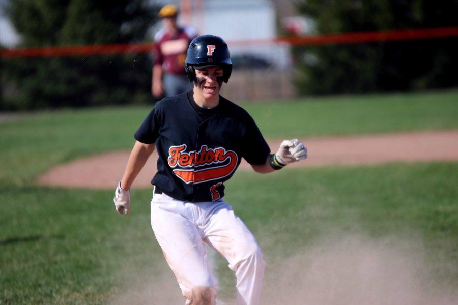 Scoring for his team, sophomore Cameron Steeves slides onto home base during the JV Basball team's April 12th game against Davison.
