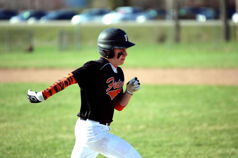 After striking the ball, freshman Brady Triola runs to first base.