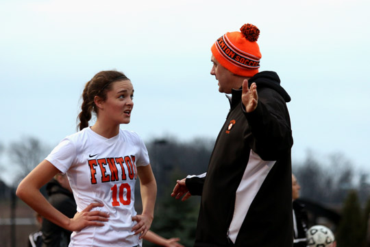 While playing in a varsity soccer game, sophomore Erin Conroy talks to coach Sullivan about how to improve. The girls lost to Swartz Creek in a close game of 0-1.