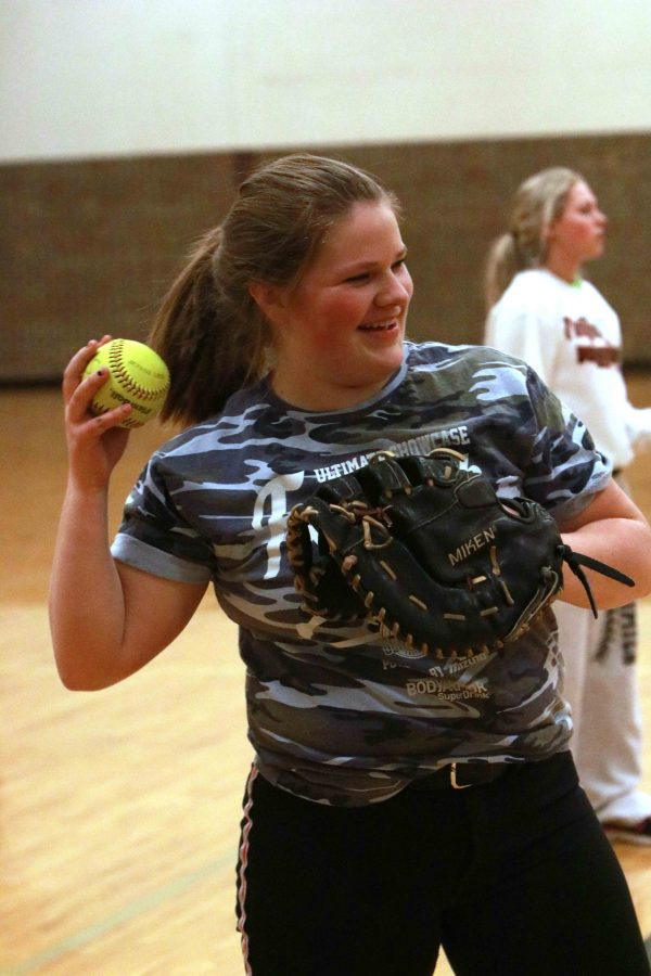 Playing catch, sophomore Natalie Thomas laughs as she throws the ball to a teammate. The team spent their practice inside because of the rainy weather to prepare for their game against Howell.