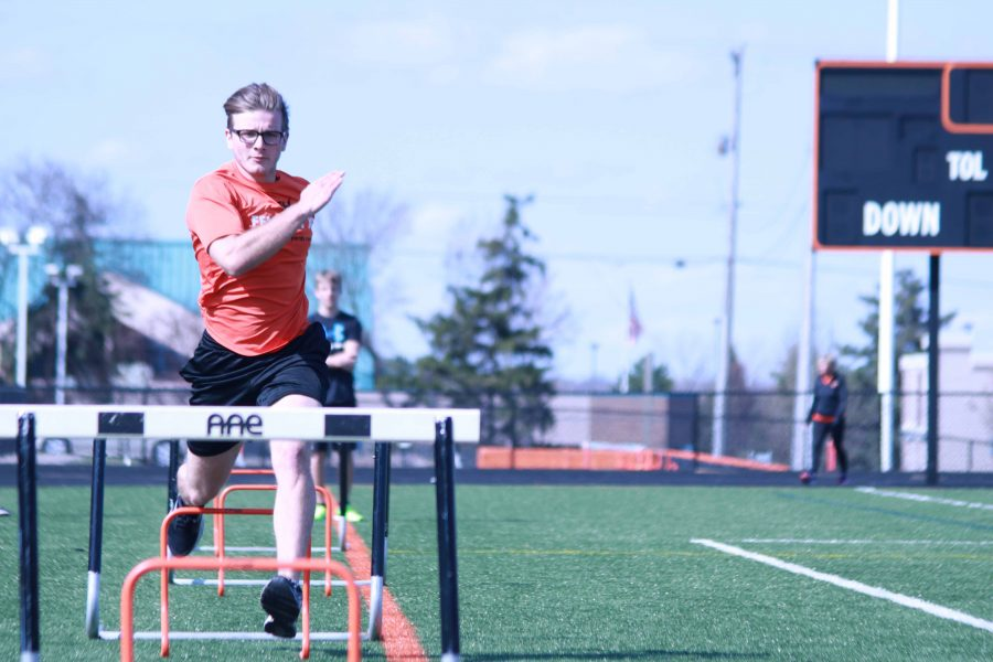 Making his way through hurdles at practice, senior Bronson Kelly successfully goes through hurdles set up in front of him. As the season just started, Kelly is very prepared to enjoy one last season with the Fenton High School track team.