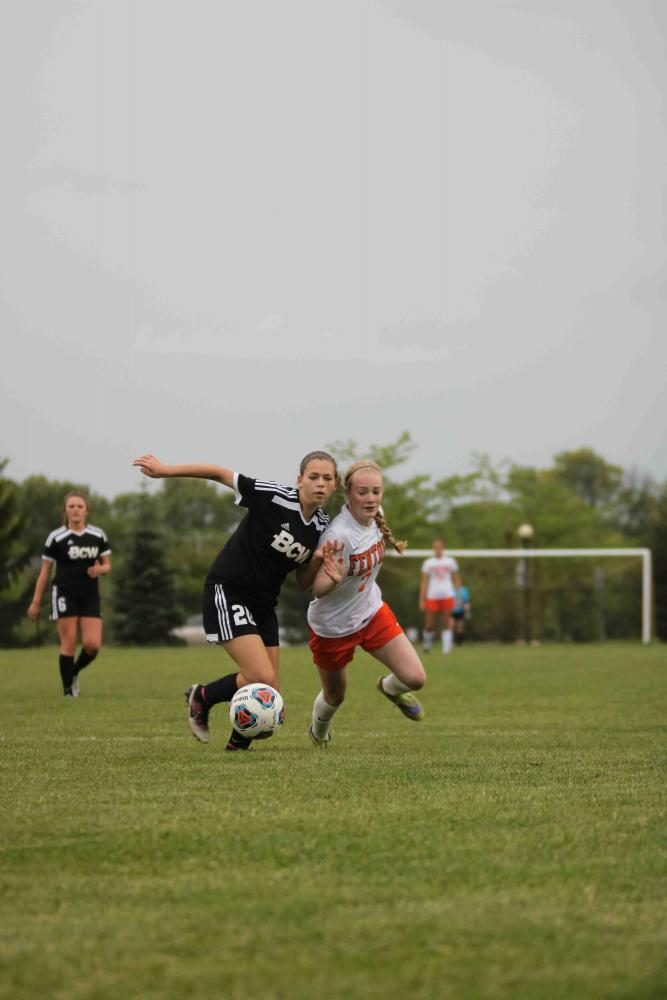 Battling for the ball, sophomore Lauren Murphy participates in the last home game of the 2017 girls soccer season. The girls pulled out the win against Bay City Western with a score of 2-1.