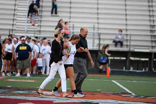 Senior Skylar Parks walking with her parents at senior night. Skylar was captain of the Fenton-Linden lacrosse team this year and is planning to play in college.