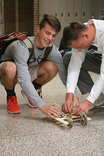 Scared to get pinched by the mouse trap, junior Chanse Setzke helps his partner junior David Pietryga set the trap for their car race.