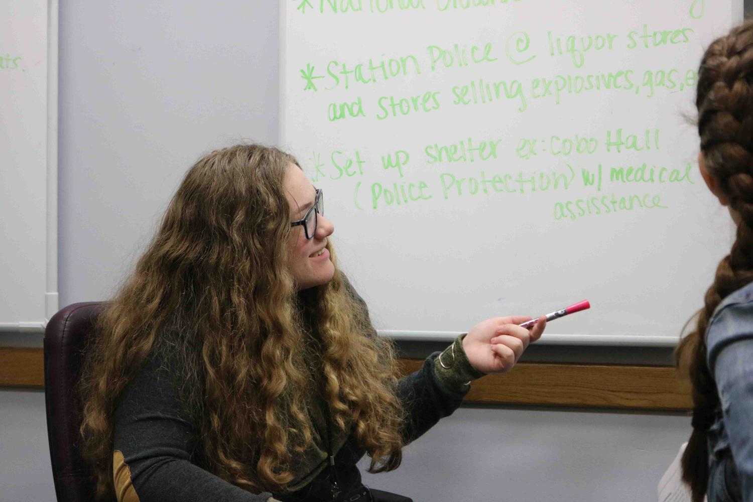 Participating in a government simulation of the Detroit riots, sophomore Hannah Ferguson points out the answer to the question they received at the beginning of the trip. The American studies class took a trip to Lansing Michigan to take part in the simulation and to visit the capitol.