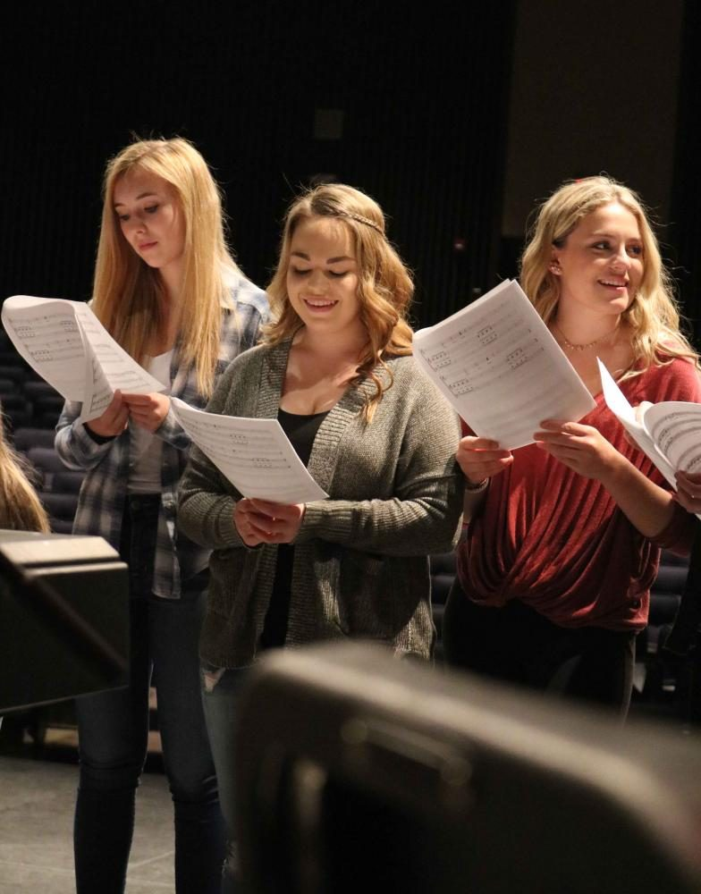 During their 3B Ambassador class, junior Kelly Canning and sophomores Emily Hayes and Alex Marsee practice their new songs for very last concert. Their last concert of the school year is on May 12 and 13.