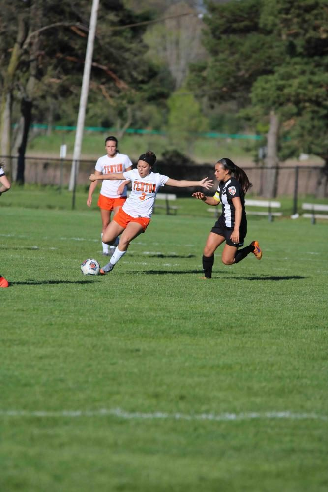 Participating in the girls varsity soccer game, sophomore Kirsten Foor steals the ball from a Flushing Raider and passes it to a fellow teammate. After the game ended in a tie, the girls went into a penalty shootout to see who is victorious.