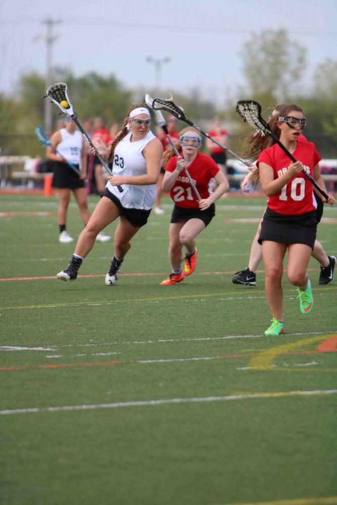 Captain Ellie Reuschlein playing offense at her lacrosse game against Swartz Creek. They won the game with a score of 8-6. This win gained the team the title of Metro League champions for the second year in a row.