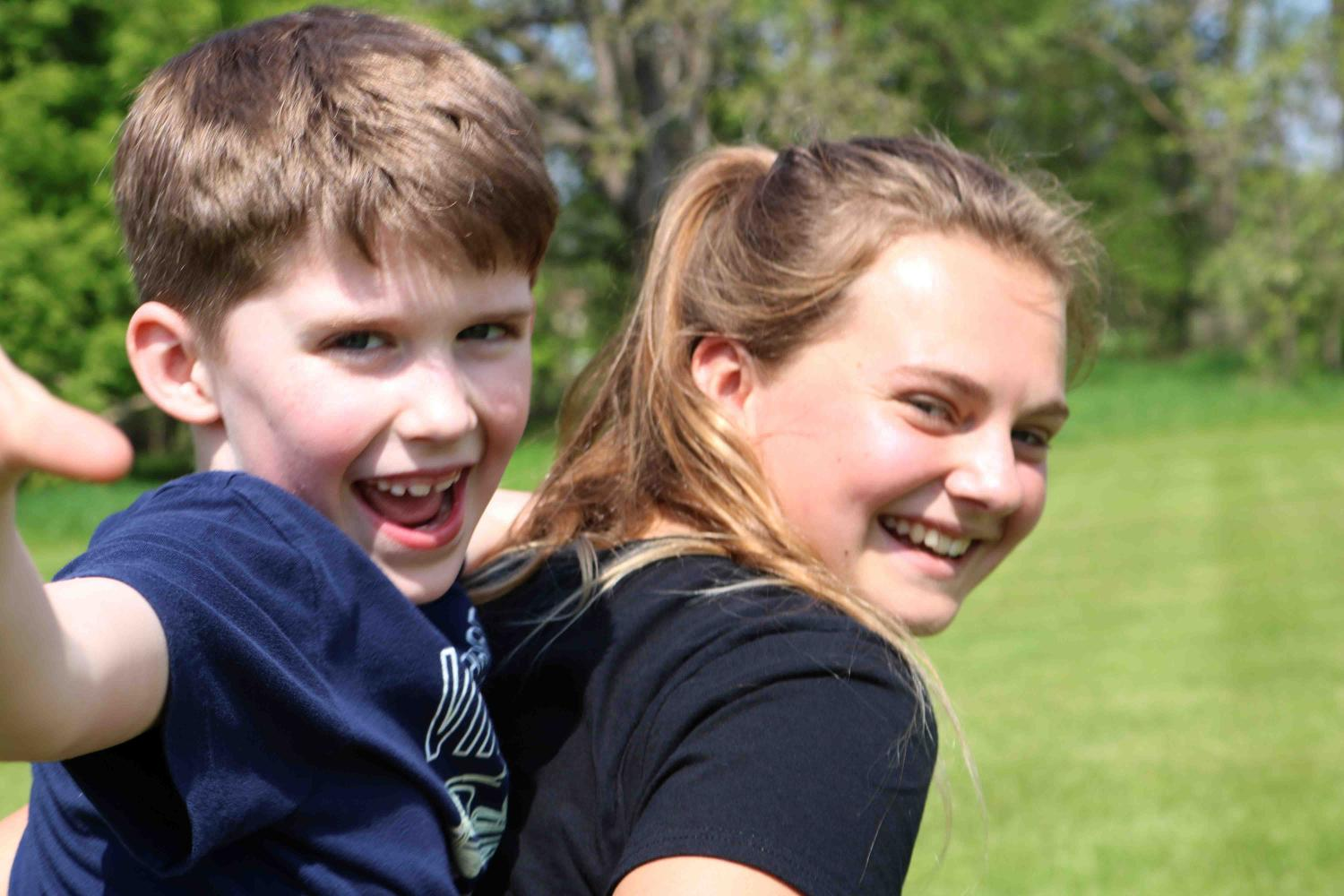 Participating in pond day, freshman Erica Behnfeldt gives a little boy a piggy back ride around while playing tag, Pond day allows high school students to interact with kids in elementary school and help them learn more about the sciences and the environment.