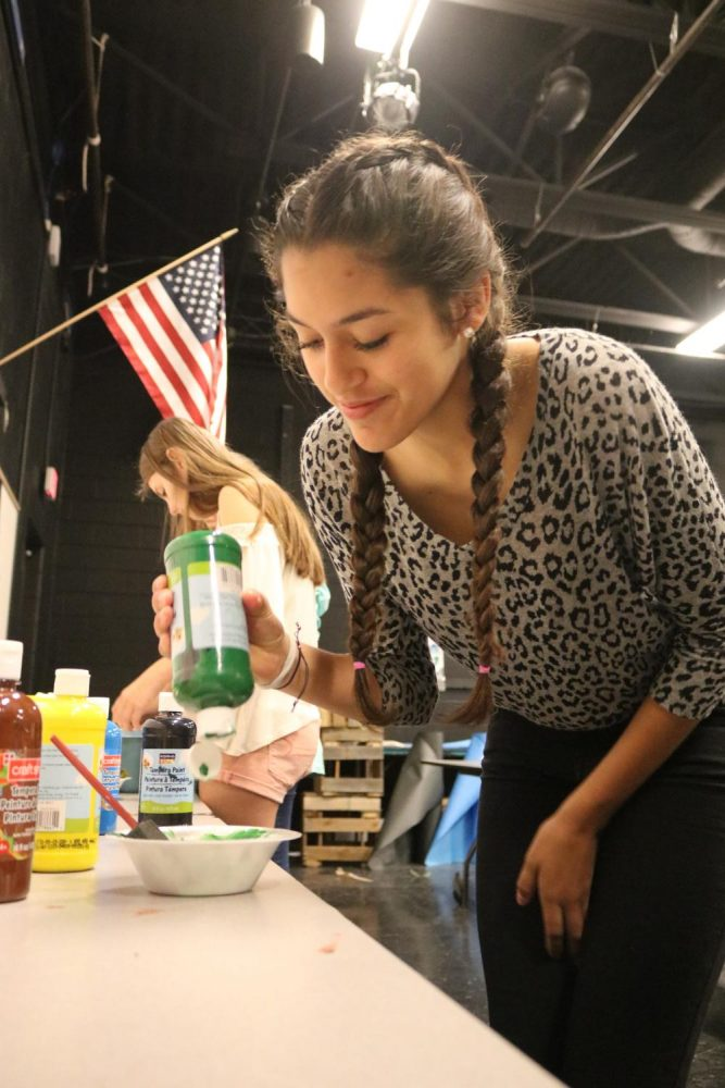 While painting back drops for her drama class, sophomore Minna Ramirez goes back to get more paint.