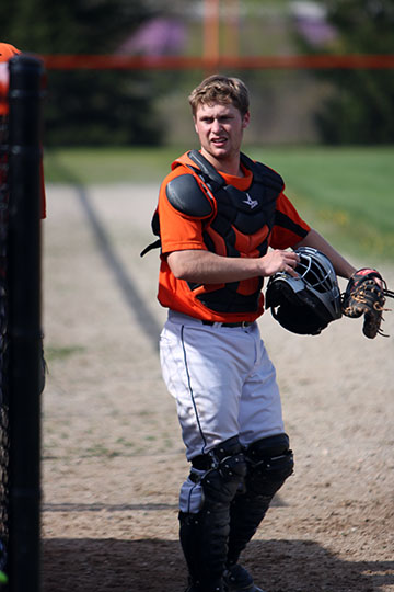 Preparing to catch, senior Jonathan Gillman grabs his pads, glove and helmet. Fenton won against holly 5-0.