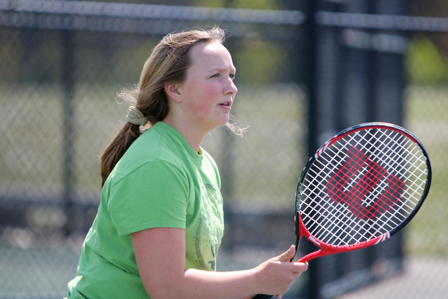 Getting ready to start up a practice match, freshman Abby Lamb keeps her eye on the ball.