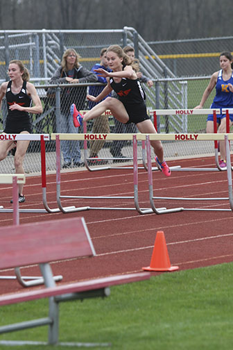 Sophomore Cassie Campbell jumps as high as she can and clears the hurdle. The girls track team beat Holly and Kearsley at the away meet.