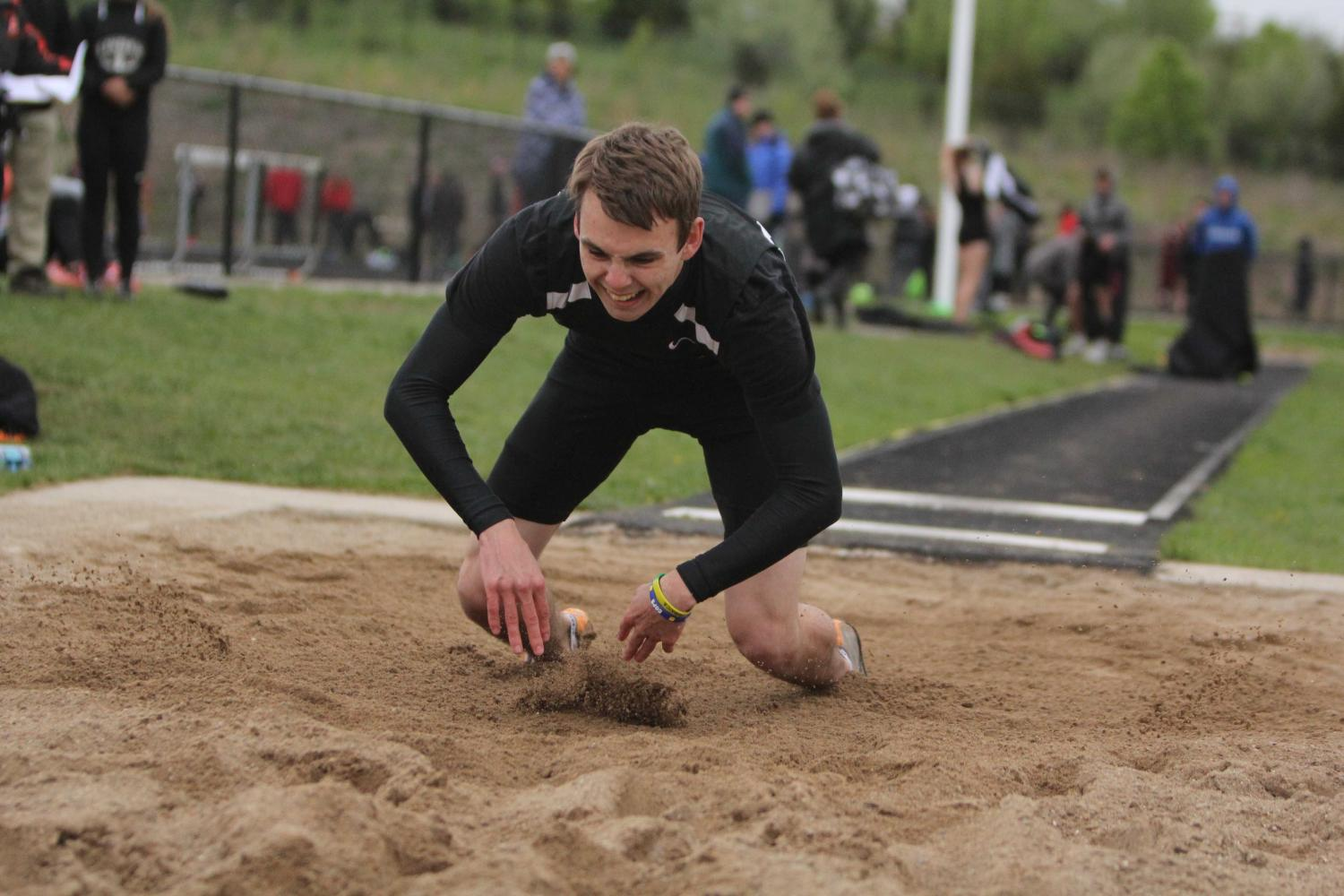 Laughing during the long jump, senior Sean Stiles enjoys one of his last home track meets. After completing the long jump, Stiles smiles as he hits the sand.