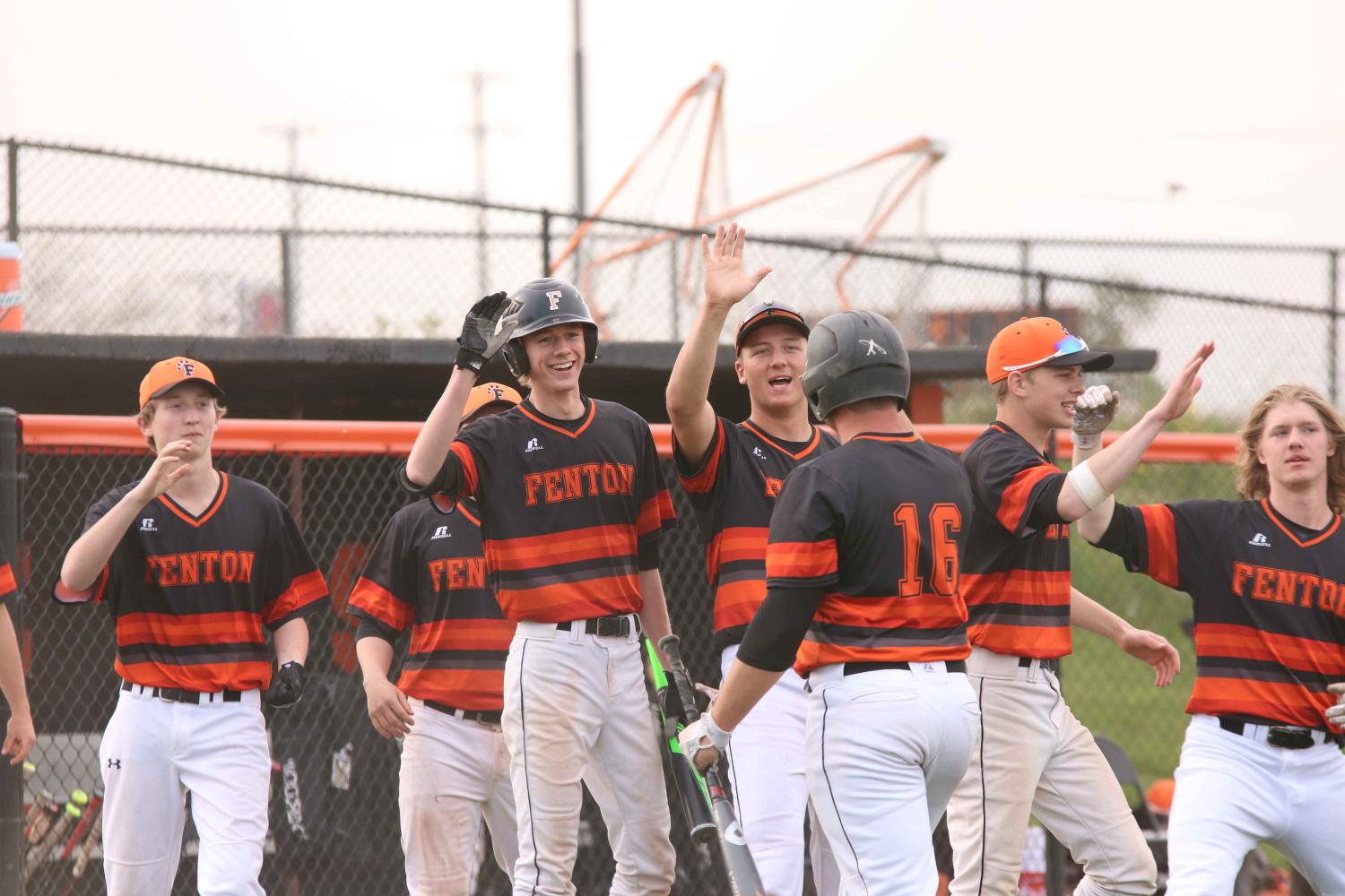 Junior Nolan Lawrence high fives teammate after receiving a run.  The varsity baseball team beat Lake Fenton 14-6 on May 10.