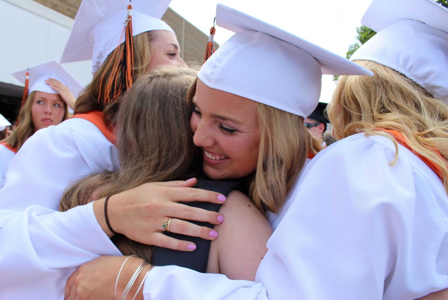 After the graduation ceremony is completed, junior, Maya Mead gets wrapped in a hug from her friend, senior, Lauren Gruber. Although it was 95 degrees out, it didn't stop Mead from saying goodbye and supporting her senior friends.