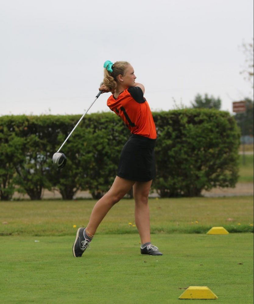 During a match up against Swartz Creek, freshman Brook Herbstreit finishes her swing after teeing off.