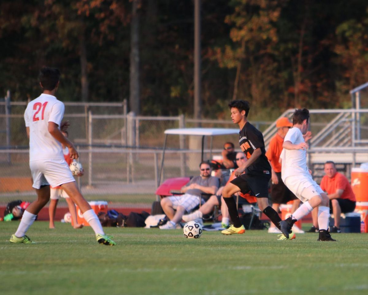 Kicking the ball onto the field, junior Billy Petsch keeps the ball from the opposing team.