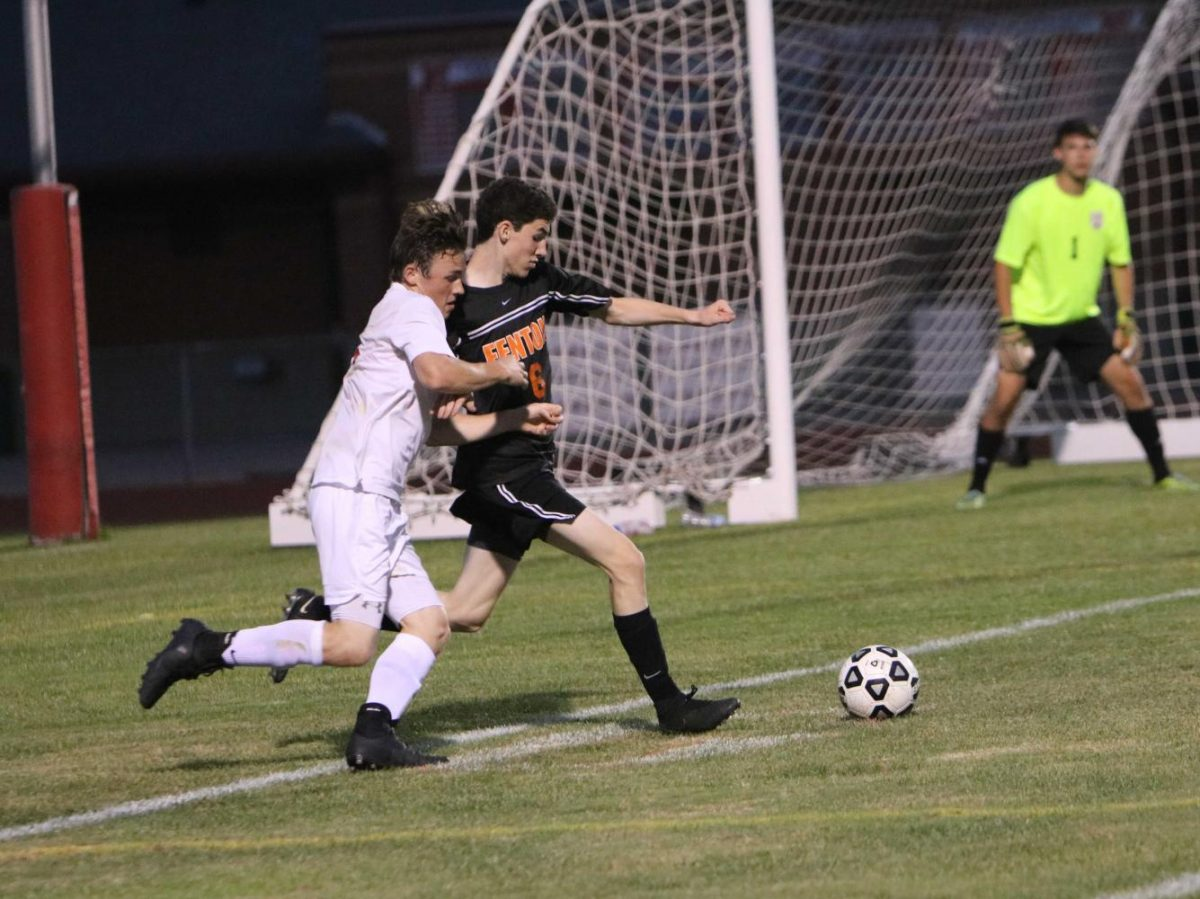 Senior Owen Koza keeps the ball from his opponent.