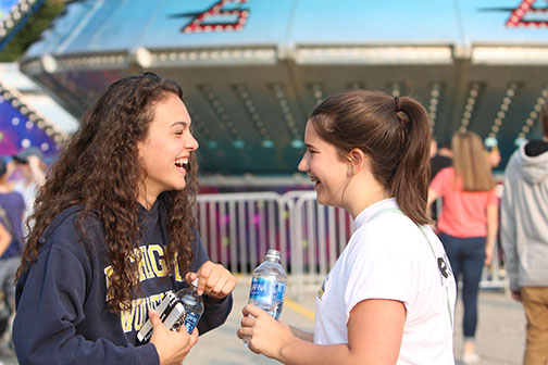 Sophomores Regina Pauly and Elizabeth Goodman laughing at the St. Johns Applefest. The two went to the fair on Friday and Saturday.