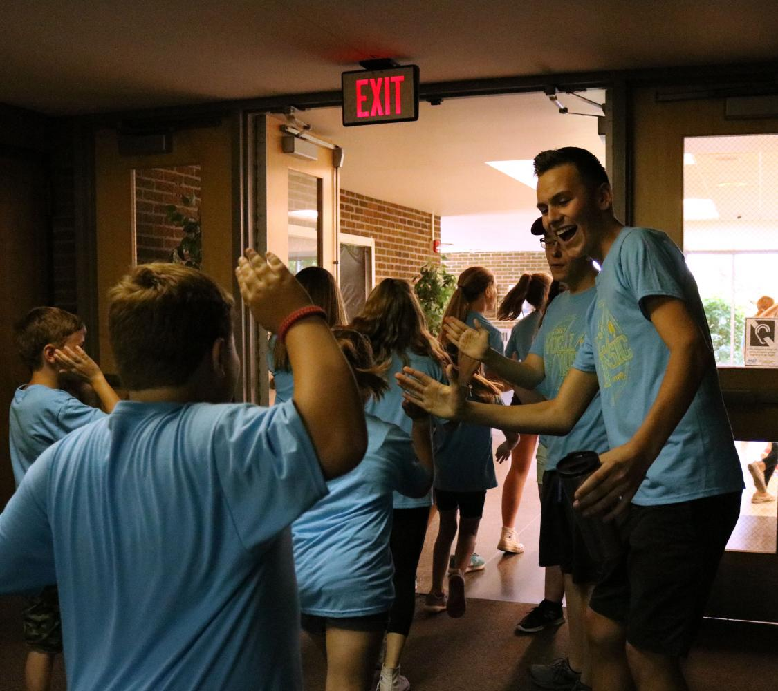 Senior, Tyler Dunn high-fives elementary and middle school students as they leave from their junior ambassador concert. The concert was a huge success with parents flooding the auditorium and the hall outside.