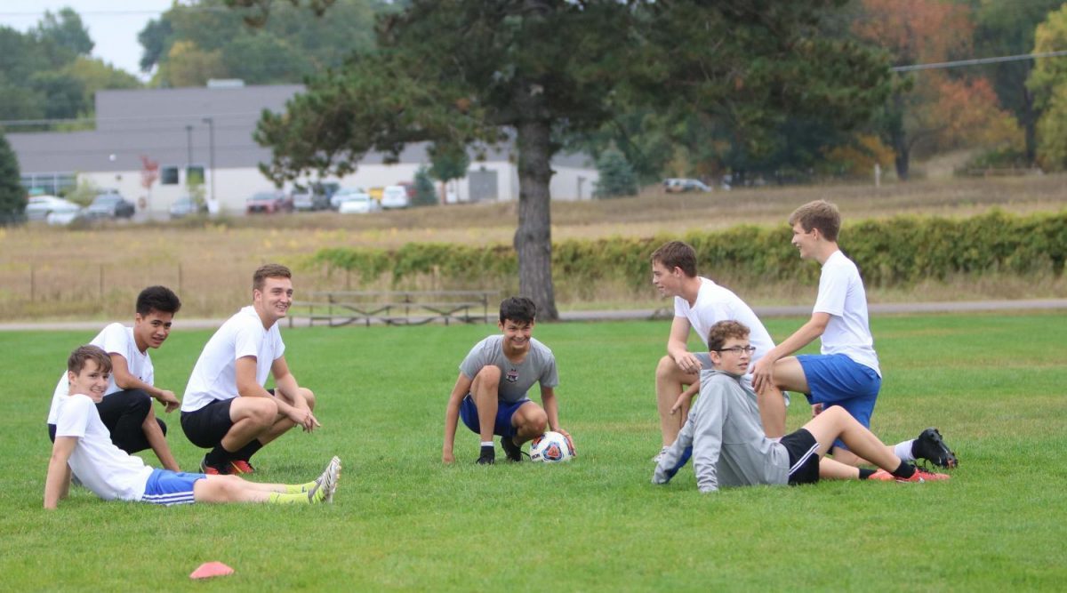 During their shared soccer practice, JV and varsity soccer players finish their soccer activity by sitting down.