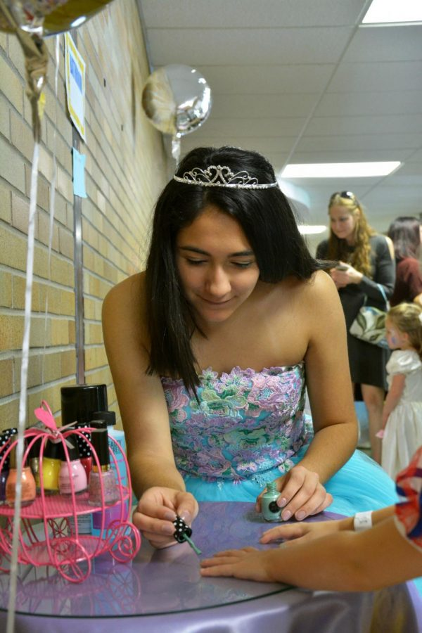 While volunteering at the princess ball, senior Arianna Mansour paints nails of the young princess's attending the ball. The National Honors Society members volunteer their time every year when the ball comes to town.