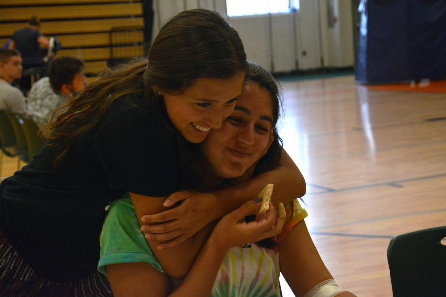 Reunited at his summers blood drive, senior Libby Carpenter hugs junior Delaney Miesch after she gives blood. this was the school's first blood drive with Michigan Blood.