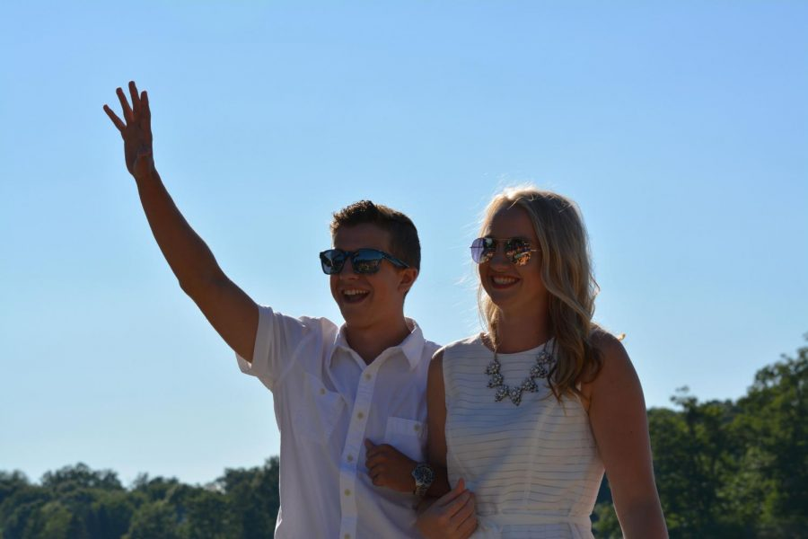 Waving to the crowd, senior Jacob Taylor shows his excitement along side senior Molly Gundry during the crowning of the freedom festival king and queen. Both Taylor and Gundry were crowned King and Queen at the silver lake ski show over the summer.