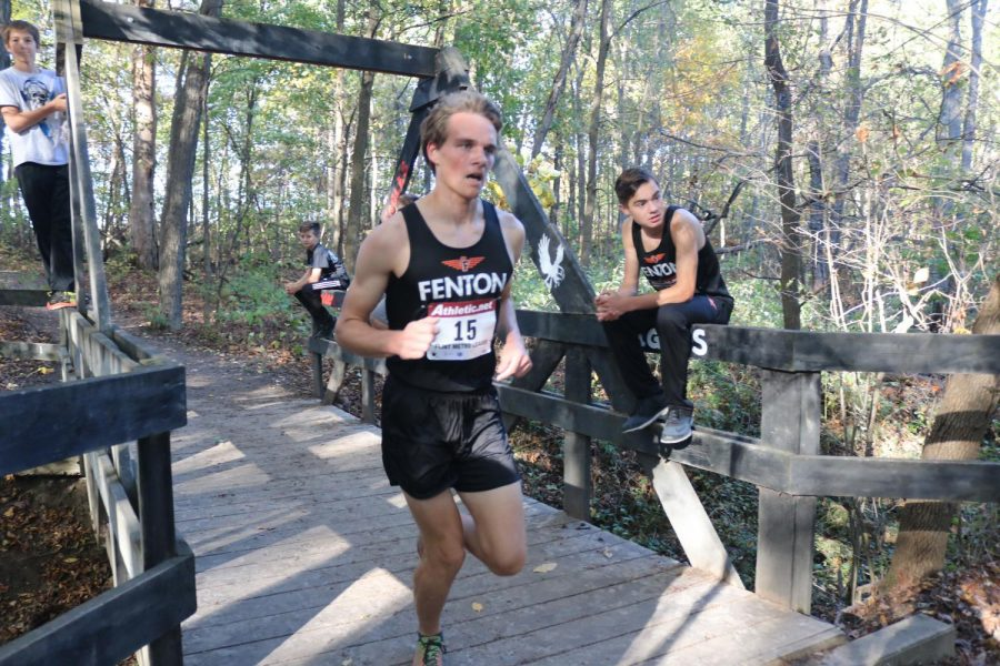 Making his way across the bridge, senior Mitchell Chabot pushes towards the end of Linden's course. The boys varsity cross country team placed in the top 17 spots at the meet, making eight runners All-Metro.