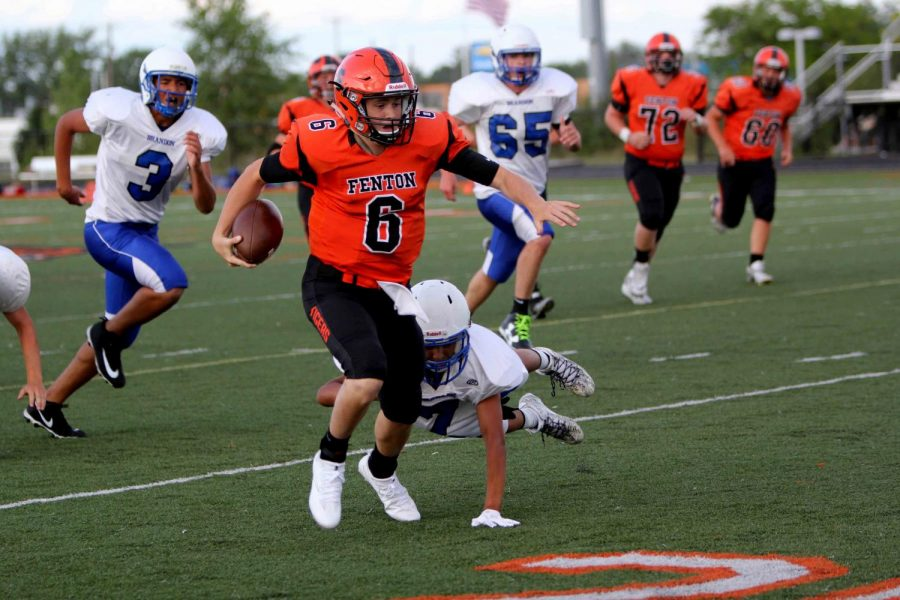 On the run with the football freshman quarterback , Dylan Davidson  gains yards hoping to get a first down for his team. JV Fenton football team won their first game against Brandon.