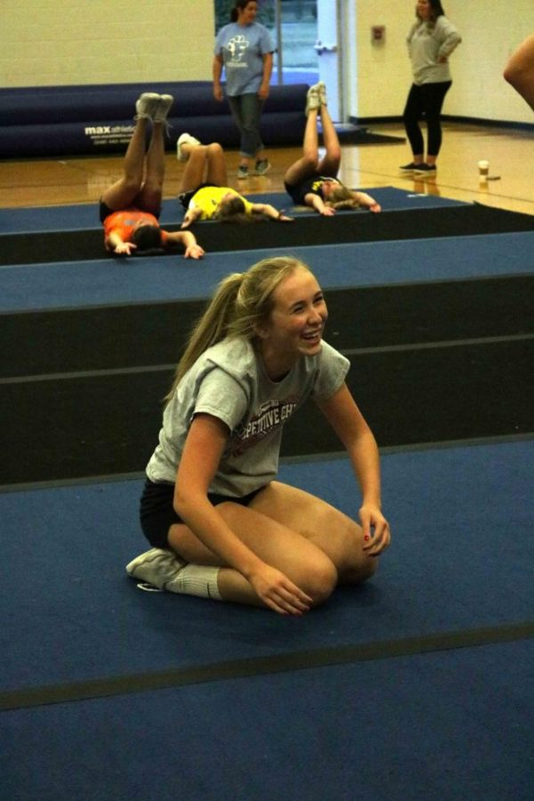 While laughing at a joke, senior Kelly Canning practices stunts with her cheer team on Oct 10.