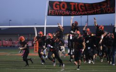 The boys varsity football team starts off the game by entering under the banner.