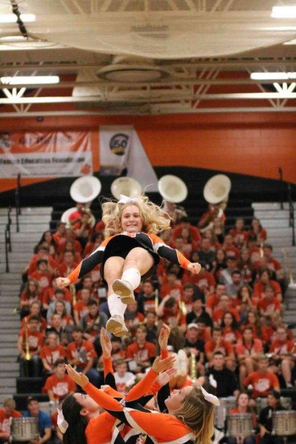 Cheering in the pep assembly, senior Rachael Roman continues to flash a smile during her nearly flawless stunt . The varsity cheer preforms a routines every pep assembly to wow the crowd.