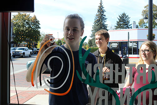 Junior Jackson Racette along the rest of Key Club paints the windows of Northern Country Chic in downtown Fenton along with other businesses in preparation of homecoming week.