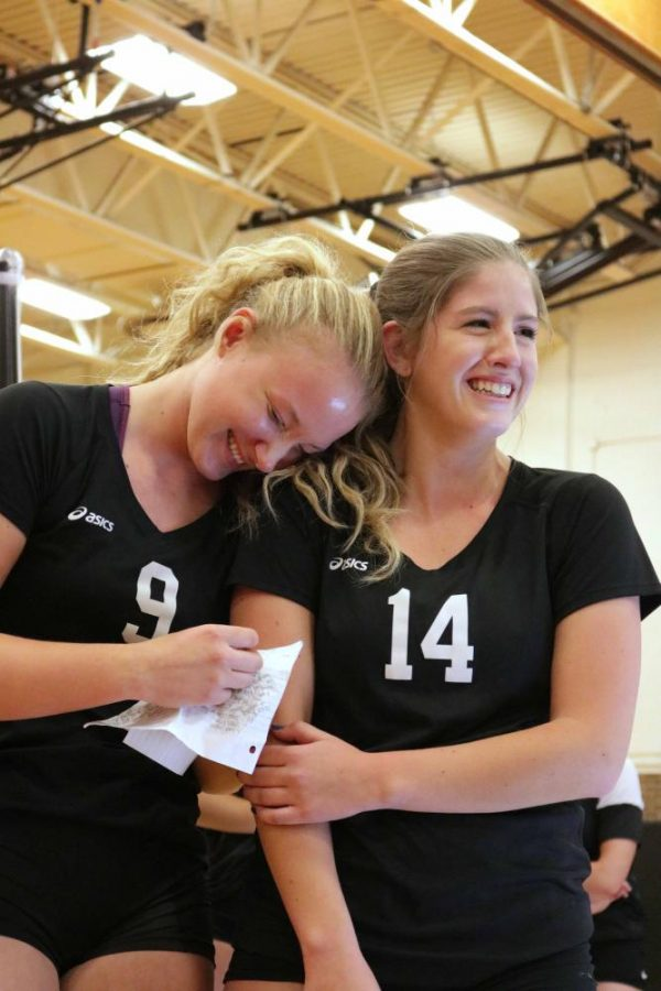 Sophomore Lydia Podlesak and senior McKenzie Lookebill laugh at the junior Anna Janowak's (not pictured) note to Lookebill.  It was parent and senior night at the freshmen, JV and varsity volleyball games on Oct. 17.