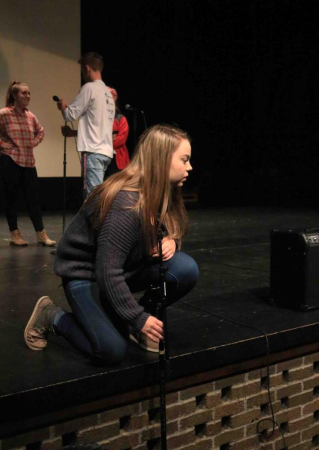 Junior Emily Hayes helps set up the mics for the next audition. the IB theater students produced a fantastic talent show that consisted of acting, comedy, dancing, instruments, and singing.